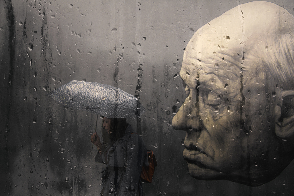 berlin wall head street art rain umbrella grey girl