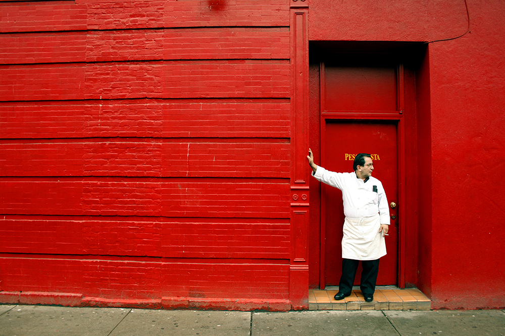 man smokes cigarette in new york red wall